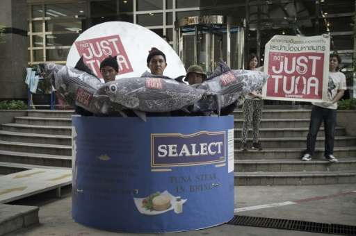 Greenpeace activists stand inside a large mock-up of a canned tuna in front of the Thai Union headquarters in Bangkok on October