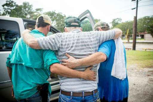 Harvey Dubois, 76, is helped by rescue teams that helped save him from his flooded home in Orange, Texas