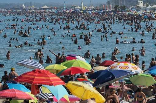 Holidaymakers seek to escape the heat taking to the beaches from southern France to Italy