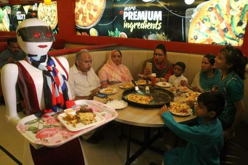 In this photograph taken on July 4, 2017, a robot waitress delivers food at a pizza restaurant in Multan
