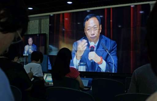 Journalists (in foreground) watch a large video screen showing Terry Gou, founder of Foxconn parent Hon Hai group, during a shar