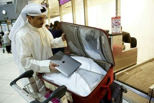 Kuwaiti social media activist Thamer al-Dakheel Bourashed puts his laptop inside his suitcase at Kuwait International Airport in