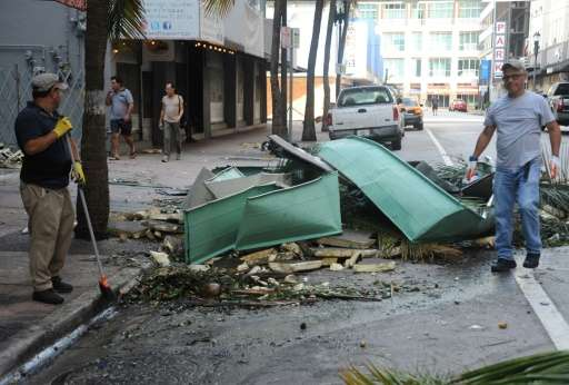 Miami residents clean up debris in the street in the aftermath of Hurricane Irma