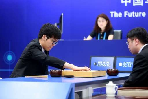Nineteen-year-old Go player Ke Jie (L) makes a move during the first match against Google's artificial intelligence programme Al