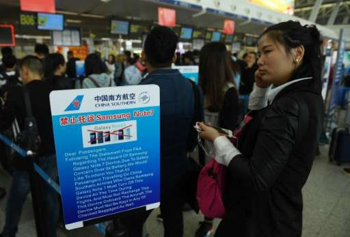 Passengers line up beside a safety warning about the Samsung Galaxy Note 7 smartphone at China's Wuhan airport in this October 2