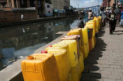 People stand beside 20 litre jerrycans waiting to be filled at a public fountain during a period when the public water supply ha