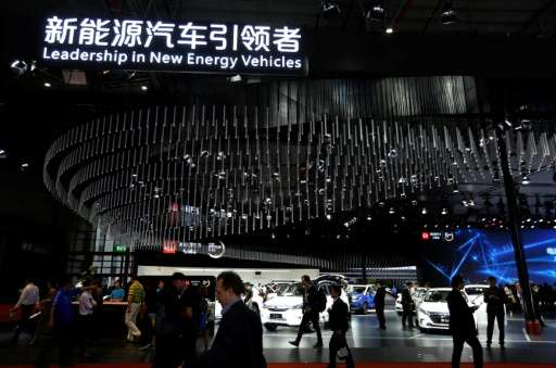 People visit the 'new-energy' vehicles area at the Shanghai Auto Show on April 19, 2017. With a quota threat looming, major manu
