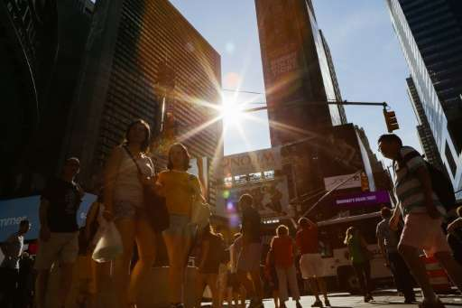 People walk around Times Square during a sunny day as hot temperatures continue in New York on July 21, 2017