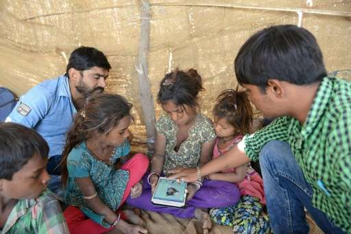 Sheltered beneath a canvas sheet, miles from any roads or power lines, children huddle around a tablet and experience the intern
