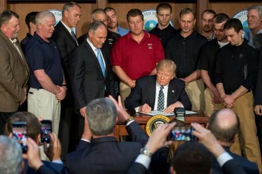 """Surrounded by miners, President Donald Trump signs an order on Tuesday he said would end the """"war of coal"""" by rolling"""