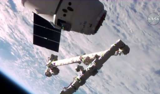 The Canadarm2 robotic arm is poised to grab the unmanned SpaceX Dragon cargo capsule in this NASA TV video grab from June 5, 201