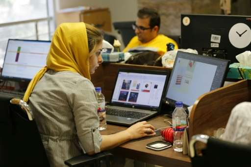 This file picture taken on July 09, 2017 shows employees at an e-commerce site's offices in the Iranian capital Tehran