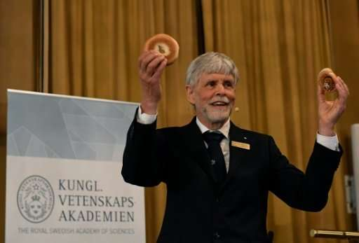 Thors Hans Hansson, a member of the Nobel physics committee, uses a cinnamon bun, a pretzel and a bagel to explain the field of
