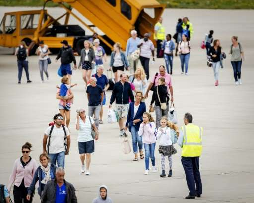 Tourists arriving with the first flight from Sint Maarten, walk on the tarmac at the Eindhoven Military Airbase