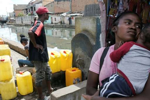 Water carrier LŽo (left) fills up a jerrycan in Antananarivo. Campaign group WATERAID says 65 percent of Madagascar's rural popu