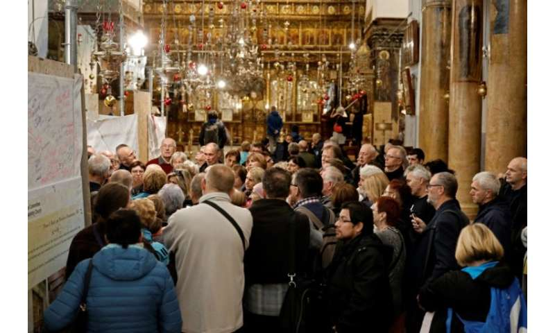 A group of tourists and pilgrims visit the Church of the Nativity, the place where Jesus is said to have been born, in the Bibli