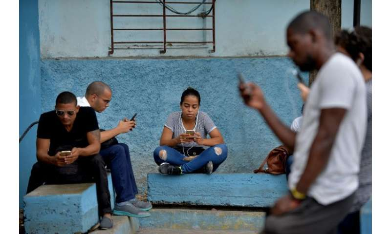 People use their mobile phones to connect to internet through WiFi at a park in Havana