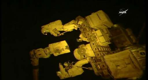 Spacewalking astronauts give new hand to robot arm