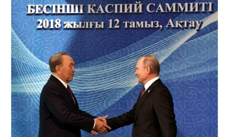 Russian President Vladimir Putin and Kazakhstan's President Nursultan Nazarbayev shake hands at the 5th Caspian Summit in Aktau