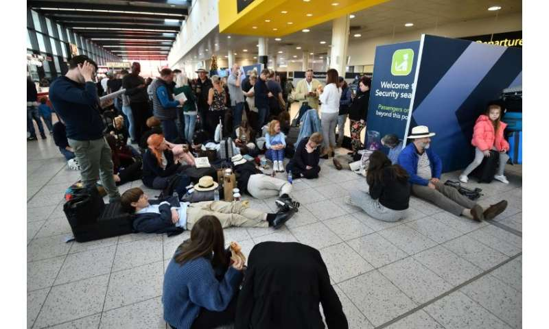 Passengers wait at the North Terminal at London Gatwick Airport,as police frantically searched for the operators of the drones t