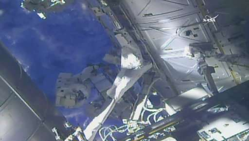 Spacewalking astronauts perform pump swap at space station