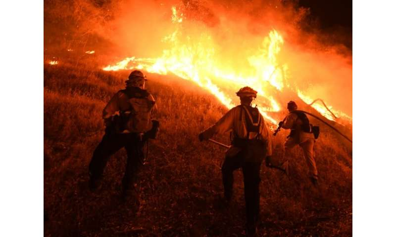 Firefighters conduct a controlled burn to defend houses against flames from the Ranch fire, as it continues to spreads towards t