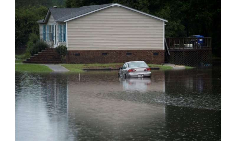 A car is partially submerged in floodwater near a house in Grifton, North Carolina