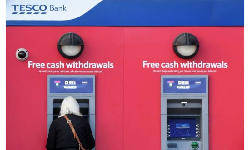 A customer uses an RBS branded automated teller machine (ATM), at a Tesco Bank cash point, in Liverpool, north west England, on