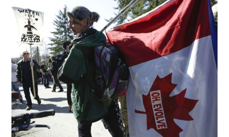 A demonstrator carrying a Canadian flag protests against the expansion of Texas-based Kinder Morgan's Trans Mountain pipeline pr