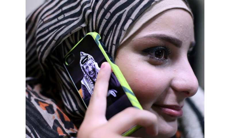 A file picture shows a young Palestinian woman using a mobile phone in the West Bank city of Ramallah on November 5, 2014