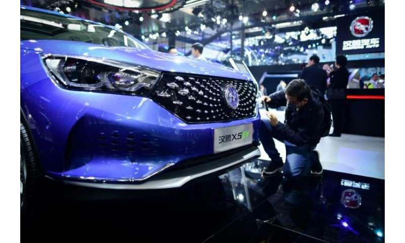A man takes a photo of Hanteng X5 EV car at the Beijing auto show