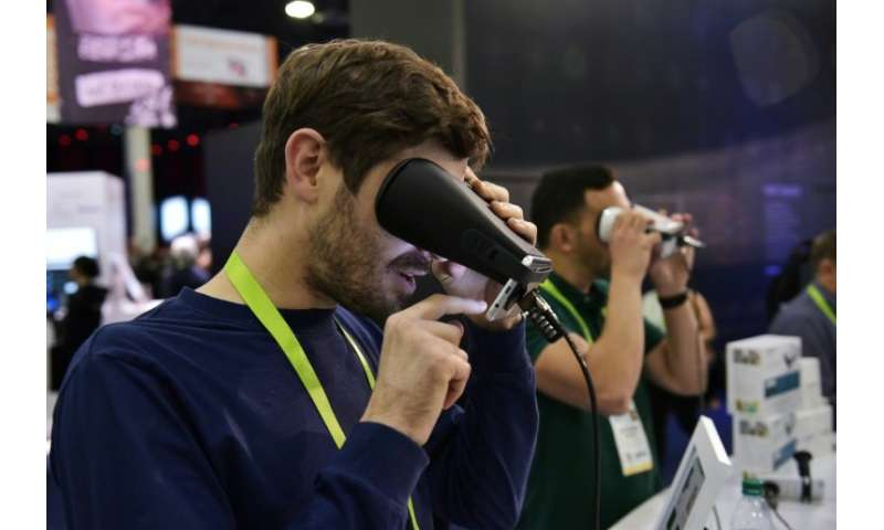 A man tries out the EyeQue Insight home visual acuity screener at the 2018 Consumer Electronics Show
