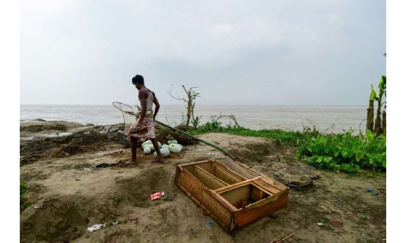 A man walks through the remains of a home next to the eroding banks of the Padma river in Bangladesh's Rajshahi district