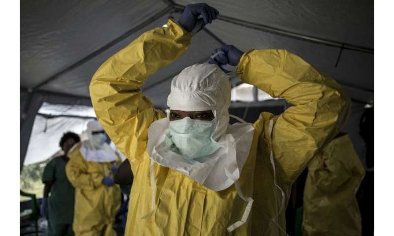 A medical worker puts on protective gear as she prepares to enter an ebola treatment centre run by The Alliance for Internationa