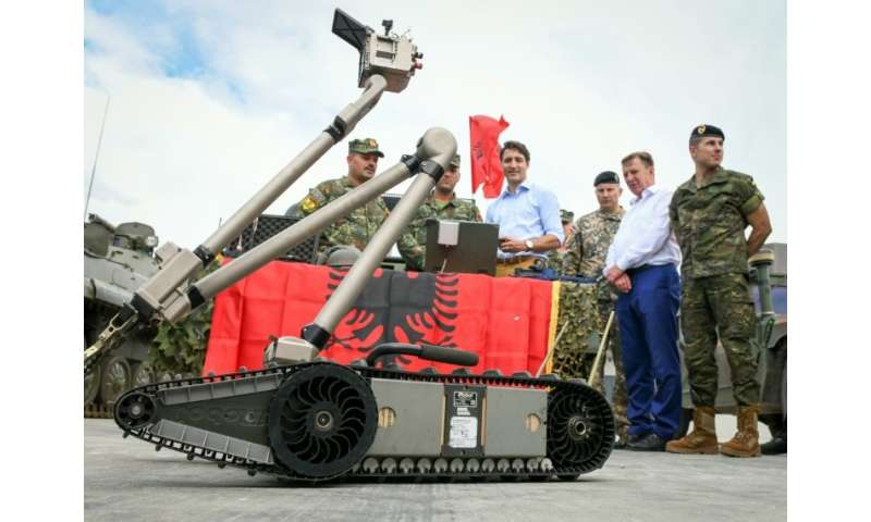 A military robot deployed with NATO troops in Latvia is inspected by Canadian Prime Minister Justin Trudeau in July 2018.