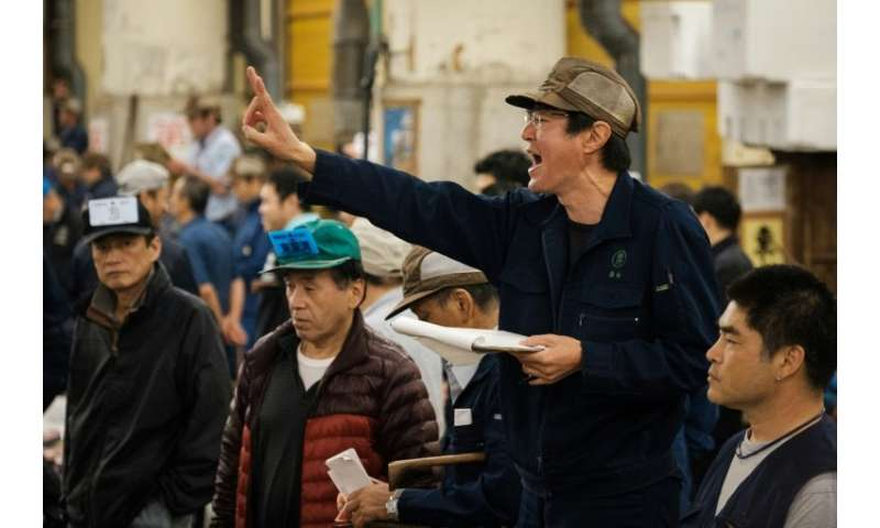 An auctioneer shouts out during the final tuna auction at Tokyo's Tsukiji fish market, which has closed its doors to relocate to