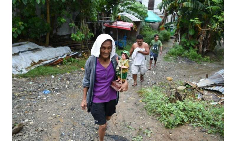 An elderly resident carries a religious icon as she evacuates to a safer place as Typhoon Mangkhut approaches the city of Tugueg