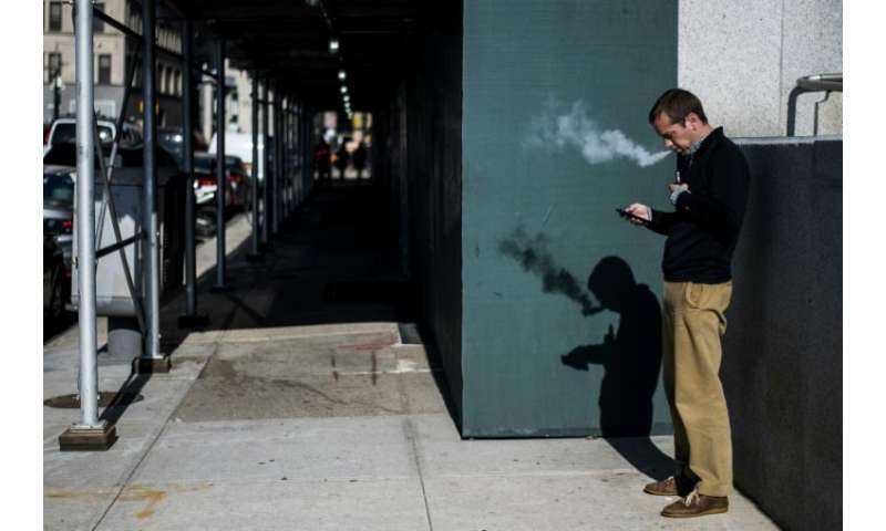 A New York man puffs away on his electronic cigarette. E-cigarettes may encourage youths to start smoking but may also help adul