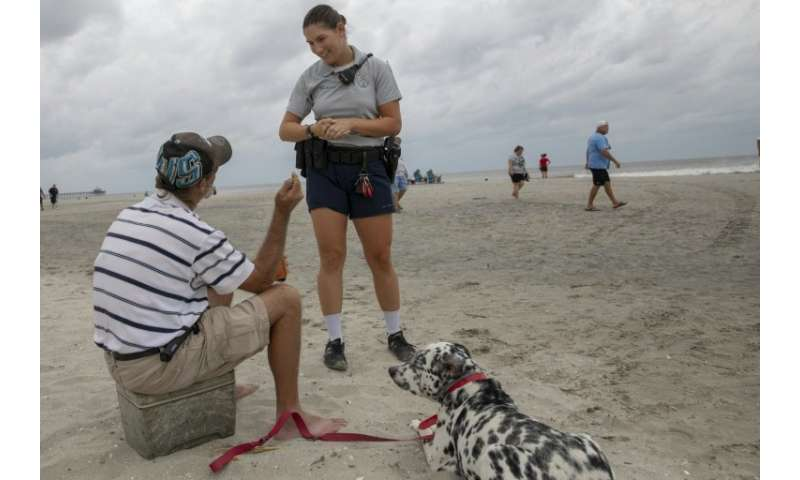 A North Myrtle Beach Police officer warns a beachgoer about the dangers of remaining on the beach as Hurricane Florence moves cl