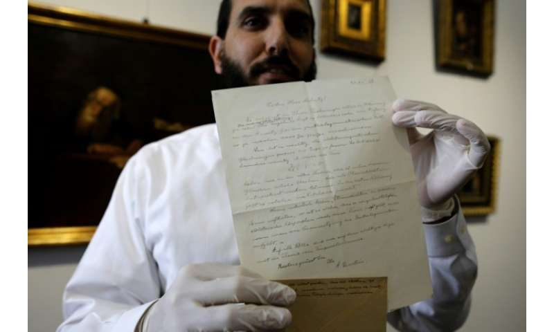 A picture taken on March 6, 2018 in Jerusalem shows an auctioneer holding up a letter by Nobel Prize-winning physicist Albert Ei