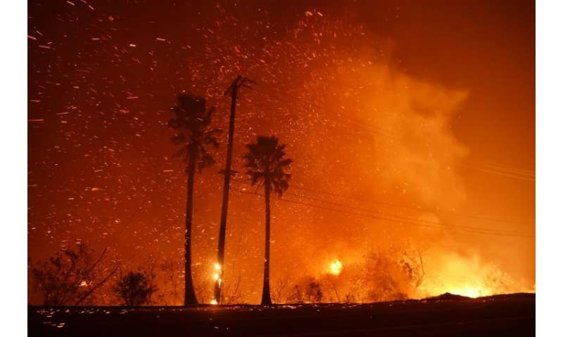 A power line catches fire as the Woolsey fire burns on both sides of Pacific Coast Highway (Highway 1) in Malibu, California, as