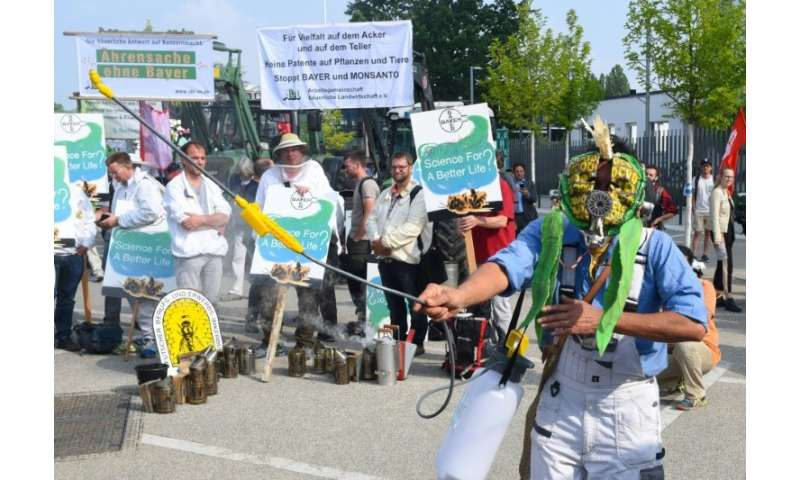 A protester wears a bee mask and holds a weed sprayer at a demonstration against the takeover of US seeds and pesticides maker M