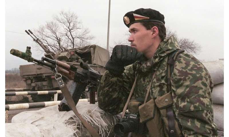 A Russian special police officer with a Zenit camera around his neck seen standing guard in February 2000 at a Chechen-Ingush bo