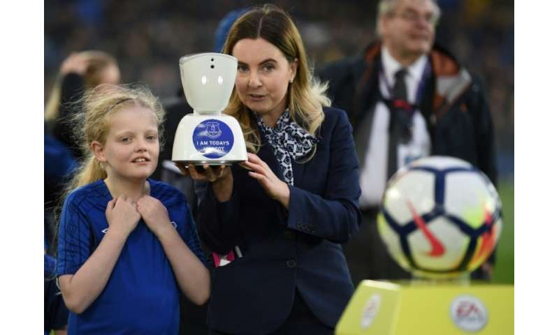 A staff member holds an AV1 telepresence robot, allowing teenage fan Jack McLinden to be a 'virtual matchday mascot' ahead of th