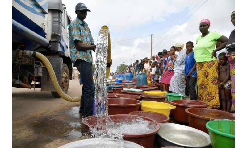 A supplier distributes water from a tanker truck to residents of Bouake at the start of July 2018