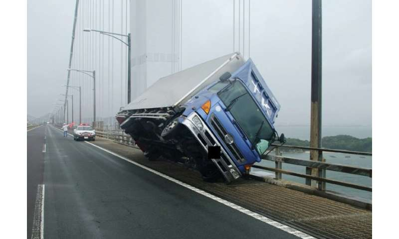 A truck sits at an angle on a bridge after being blown over by strong winds caused by Typhoon Jebi in Sakade, Japan