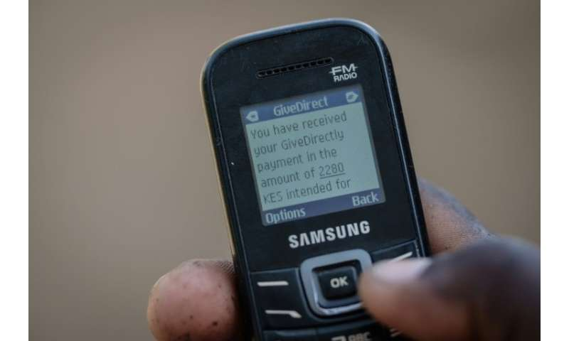A villager shows his mobile phone's monitor displaying a message confirming the universal basic income transaction, 2,250 shilli