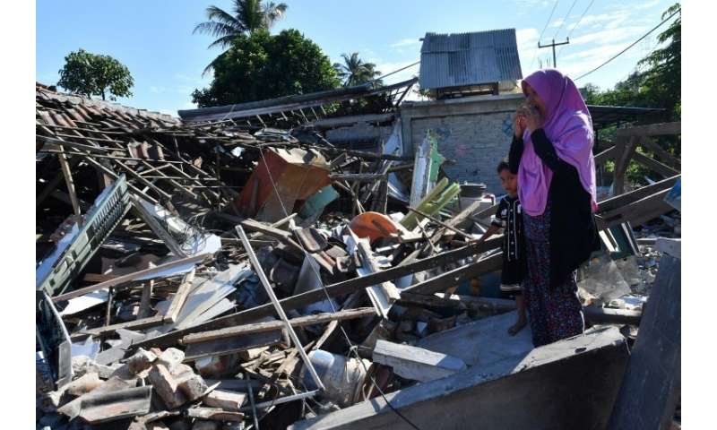 A woman and boy watch as men clear the wreckage of houses damaged by an earthquake in Menggala, North Lombok