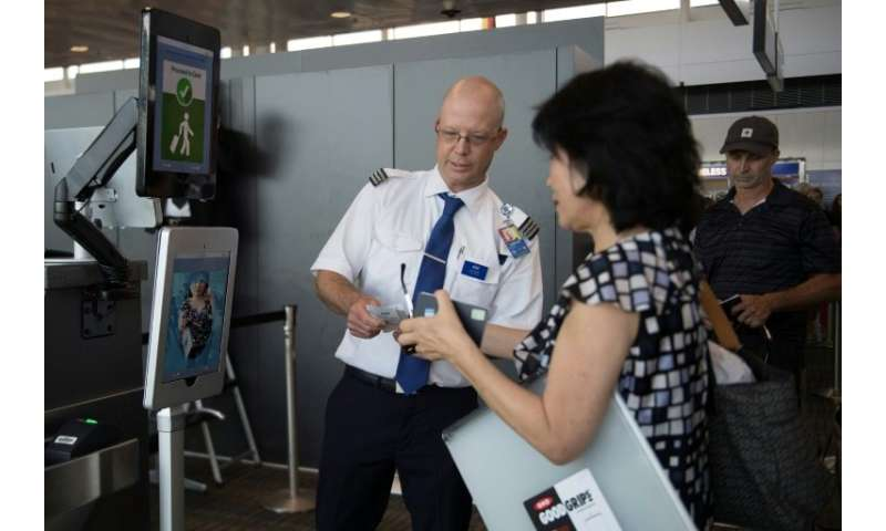 A woman boarding an SAS flight to Copenhagen goes through a facial recognition verification system at Dulles International Airpo