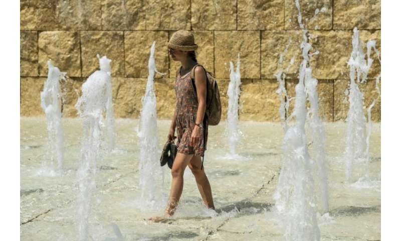 A woman cools herself in a fountain near the Ara Pacis monument in central Rome